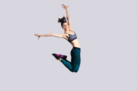 Foto de One happy attractive gorgeous young fit modern woman in aquamarine sportswear with ponytail working out, dancing, jumping with joy, full length, studio image on gray background - Imagen libre de derechos