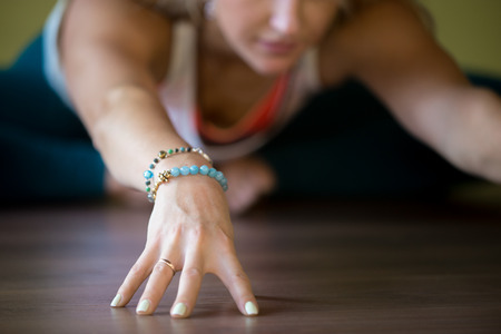 Sporty beautiful blond young woman working out indoors, doing Butterfly Pose, sitting in Purna Titli or Baddha Konasana Posture, full length, close-up, focus on hand