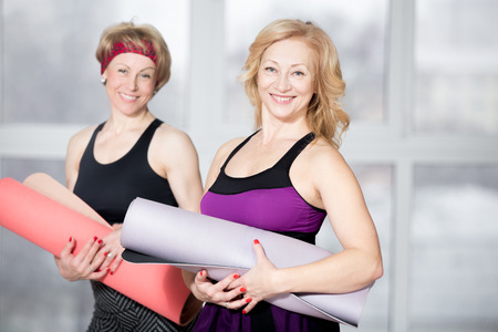 Foto de Indoor portrait of group of two cheerful attractive fit senior women posing holding fitness mats, working out in sports club class, happy smiling, looking at camera with friendly expression - Imagen libre de derechos