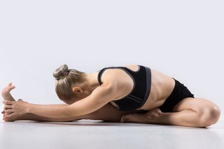 Sporty beautiful young woman practicing yoga, doing Janu Sirsasana, Head-to-Knee Forward Bend Pose, working out wearing black sportswear, studio, full length
