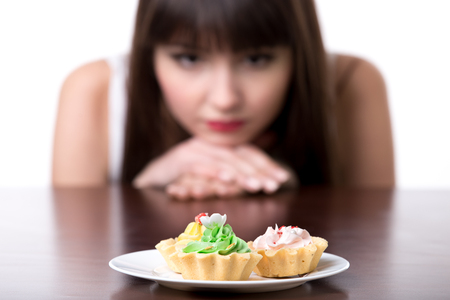 Young dieting woman sitting in front of plate with delicious cream tart cakes, looking at forbidden food with unhappy and hungry expression, studio, white background, isolated, close-up
