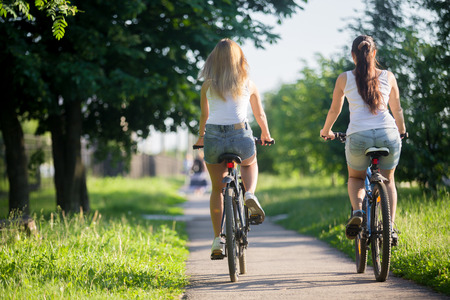 Two young women girlfriends wearing jeans shorts biking on sidewalk in park on sunny summer day, back viewの写真素材