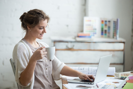 Foto de Portrait of beautiful happy smiling young designer woman sitting at home office desk with cup of coffee, working on laptop in loft interior. Attractive cheerful model using computer, typing. Indoors - Imagen libre de derechos