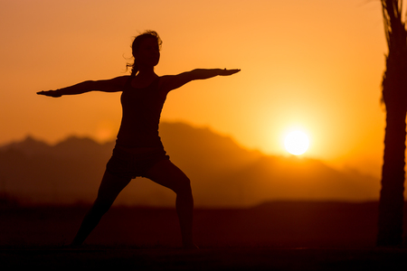 Photo pour Silhouette of young woman practicing yoga or pilates at sunset or sunrise in beautiful mountain location, doing lunge exercise, standing in Warrior II pose, Virabhadrasana 2 - image libre de droit