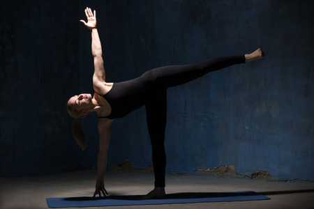 Photo pour Beautiful sporty fit young woman in black sportswear working out indoors against grunge dark blue wall. Model standing in Ardha Chandrasana posture, Half Moon Pose. Full length. - image libre de droit