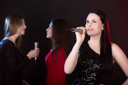 Portrait of beautiful girl singer with microphone singing lyric love song, back vocalists on the background