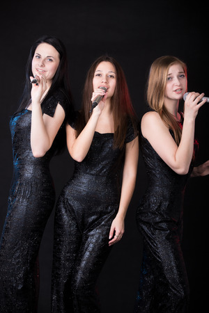 Group of three elegant beautiful young women vocalists with microphones singing, girls band performance