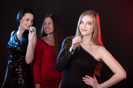 Portrait of beautiful blond girl singer with microphone, back vocalists singing with happy smiles on the background