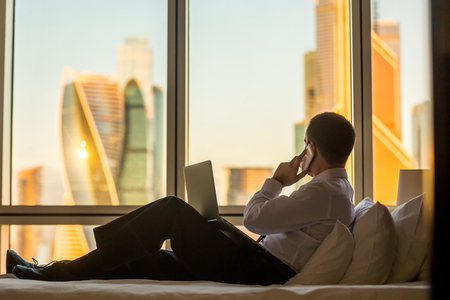 Photo for Businessperson working at home or in trip. Handsome young businessman sitting on bed with laptop and making call. Panoramic window with beautiful dawn city scenery on the background. Copy space - Royalty Free Image