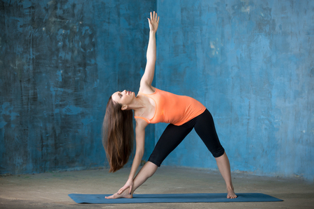 Photo pour Beautiful young woman dressed in bright sportswear enjoying yoga indoors. Doing Extended Triangle pose, Utthita Trikonasana. Full length - image libre de droit
