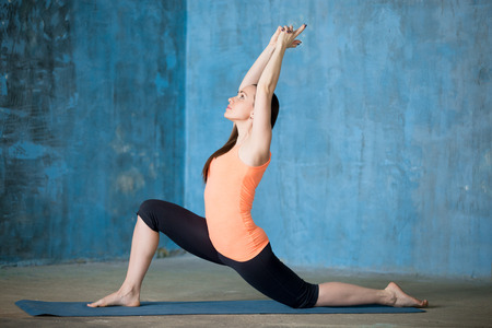 Photo pour Side view of beautiful young woman dressed in bright sportswear enjoying yoga indoors. Doing low lunge exercise, anjaneyasana. - image libre de droit
