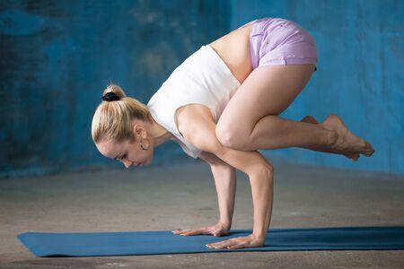 Photo pour Portrait of beautiful young woman dressed in shorts and white top enjoying yoga indoors. Crane (Crow) Pose, Bakasana. - image libre de droit