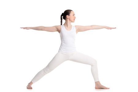 Photo pour Sporty beautiful young woman in white sportswear doing lunge exercise, Warrior II posture, Virabhadrasana 2 - image libre de droit