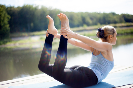 Photo pour Beautiful sporty fit blond young woman in sportswear working out outdoors in park on lake, doing backbend exercises - image libre de droit