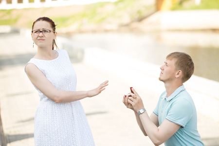 Woman refusing marriage proposal. Serious handsome young man standing on his knee offering box with engagement ring to girlfriend, asking to marry, waiting for answer. Girl turning away and saying no
