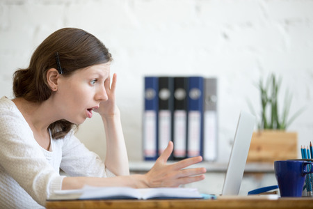 Photo pour Young stressed businesswoman sitting with laptop and touching head with shocked facial expression. Surprised business person looking at laptop computer worried and amazed with open mouth and big eyes - image libre de droit