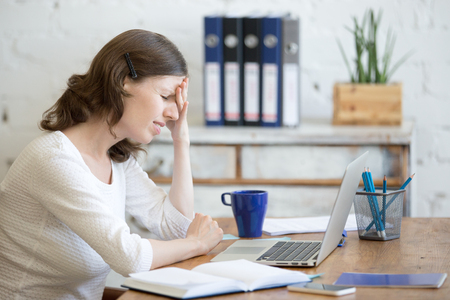 Photo pour Young stressed businesswoman sitting in front of laptop and touching head with pained expression. Business person feeling pain, suffering from migraine after working on pc, overworked or depressed - image libre de droit