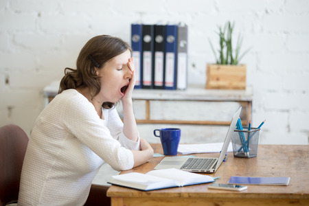 Photo for Portrait of young woman sitting at table in front of laptop, sleepy, tired, overworked, lazy to work. Attractive business woman yawning in home office relaxing or bored after work on laptop computer - Royalty Free Image