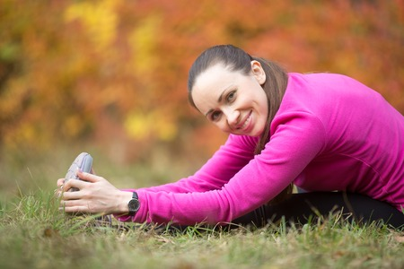 Photo pour Portrait of sporty young woman practicing yoga, doing seated Hamstring Stretch, paschimothanasana, stretching before running routine, looking at camera and smiling, working out outdoors on autumn day - image libre de droit
