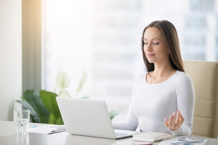 Foto de Young woman near the laptop, practicing meditation at the office desk, in front of laptop, online yoga classes, taking a break time for a minute, healing from paperwork and laptop radiation - Imagen libre de derechos