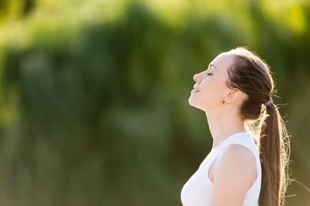 Foto de Portrait of beautiful smiling young woman enjoying yoga, relaxing, feeling alive, breathing fresh air, got freedom from work or relations, calm and dreaming with closed eyes, in green park, copy space - Imagen libre de derechos