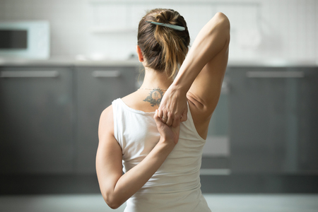 Photo pour Close up of female hands behind the back, woman practicing yoga, sitting in Cow Face exercise, Gomukasana pose, working out, wearing white sportswear, indoor, home interior background - image libre de droit