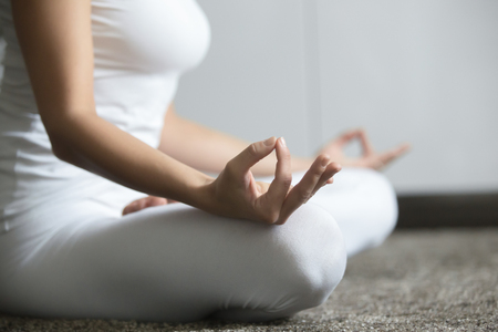 Photo pour Close up of young woman practicing yoga, sitting in Lotus exercise, Padmasana pose, working out, wearing white sportswear, home interior background. Midsection - image libre de droit