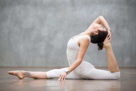 Photo pour Young pretty woman wearing white sportswear set and smartwatch working out against grey wall, doing yoga or pilates exercise. Variation of monkey god, splits, hanumanasana with backbend. Full length - image libre de droit
