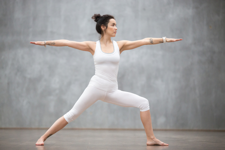 Photo pour Side view portrait of beautiful young woman wearing white tank top working out against grey wall, doing yoga or pilates exercise. Standing in Warrior two pose, Virabhadrasana. Full length - image libre de droit