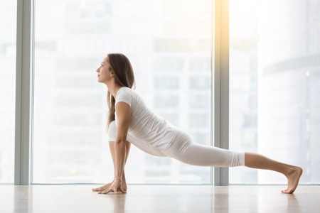Young attractive happy woman practicing yoga, stretching in Lizard exercise, Utthan Pristhasana pose, working out, wearing sportswear, white t-shirt, pants, full length, at floor window with city view