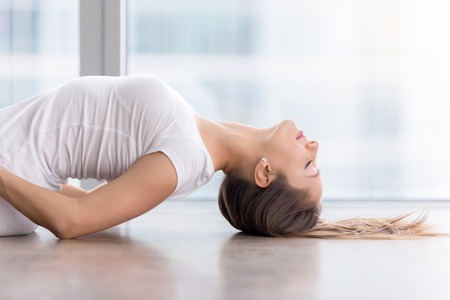 Photo pour Close up side view portrait of woman practicing yoga, lying in Fish exercise, Matsyasana pose with closed eyes, working out, wearing sportswear, white t-shirt, indoor, near floor window with city view - image libre de droit