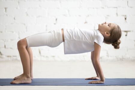 Photo pour Serious girl child practicing yoga, standing in Reverse Table Top exercise, Bridge pose working out wearing sportswear, t-shirt, pants, indoor full length, white loft studio background - image libre de droit