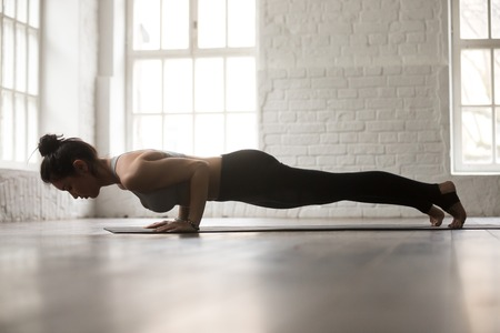 Foto de Young attractive woman practicing yoga, standing in chaturanga dandasana exercise, four limbed staff, Push ups or press ups pose, working out, white loft studio background, full length, side view - Imagen libre de derechos