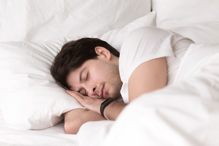 Photo pour Man is asleep in cozy white bed at night, handsome young guy sleeping at home with wearable electronic device smart watch on his wrist for sleep tracking, monitoring heart rate for healthcare - image libre de droit