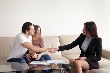 Photo pour Loving young couple shaking hands with friendly real estate agent, satisfied clients and female manager handshaking, bank loan approved, personal insurance, lease agreement, mortgage investment - image libre de droit