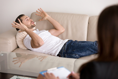 Serious troubled man at the psychologist, lying on the couch, talking and gesturing, thinking out loud, telling about his problems, trying to sort his feelings with the help of female psychotherapist