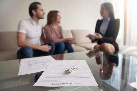 Photo pour Young renters couple sitting on couch discussing renting apartment with real estate agent, focus on rental agreement and keys, property lease contract. Looking for accommodation, long-term tenancy - image libre de droit