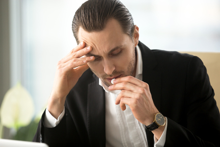 Stressed ill man touching head with hand takes white round pill from headache. Businessman tries to stop first symptoms of cold, relieve fatigue, stress with drugs help. Guy drinking medicines at work
