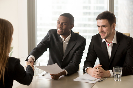 Photo for Two cheerful black and white recruiters welcoming female applicant on job interview, african and caucasian hr managers greeting candidate for vacant position, handshaking and good first impression - Royalty Free Image