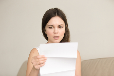 Surprised young woman reading letter with bad news. Worried attractive lady looking on document with unexpected written notice, shocked with bills, tax form or wrong payment. Message about loan debt