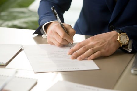 Photo pour Businessman having signatory right signing contract concept, focus on male hand putting signature on official legal document, entering into commitment, concluding business agreement, close up view - image libre de droit