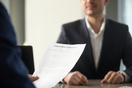Photo for Applicant holding employment agreement, considering work terms, reading position duties before signing official labor contract, successful vacancy candidate getting hired, job placement, close up - Royalty Free Image