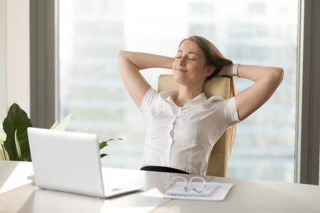 Foto de Calm smiling businesswoman relaxing at comfortable office chair hands behind head, happy woman resting in office satisfied after work done, enjoying break with eyes closed, peace of mind, no stress - Imagen libre de derechos