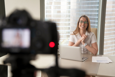 Foto de Smiling businesswoman talking on camera, happy entrepreneur vlogger recording business vlog at office desk for videoblog, filming promo ad, making presentation to website, video marketing production - Imagen libre de derechos