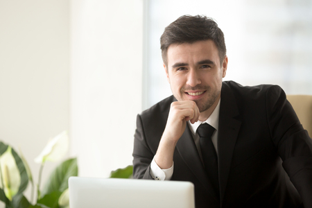 Portrait of smiling attractive consultant wearing suit posing with laptop, happy businessman working on computer, successful online business owner, stock trader or coach looking at camera, headshot