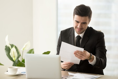 Smiling successful businessman holding document sitting at desk, reading good news in letter, reviewing beneficial lucrative contract, getting notification about bank loan or business credit approval