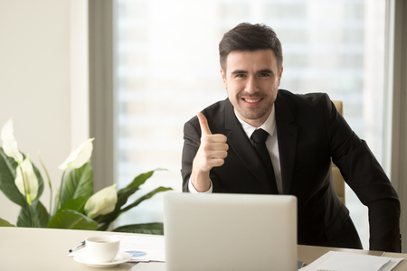 Foto de Successful confident businessman looking at camera, showing thumbs up or like sitting at office desk, effective solutions, recommending best choice for business, sign of success, good idea, great job - Imagen libre de derechos