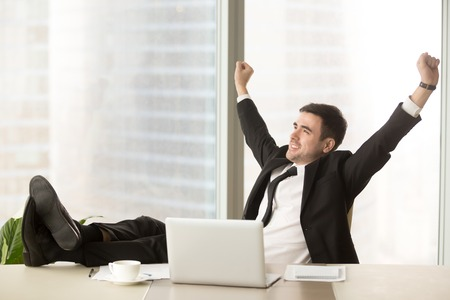 Foto de Satisfied businessman happy to finish work with laptop at office, raises hands and puts feet up on table, relaxing after hard working day in expectation of weekend leave, relaxed workday, no stress - Imagen libre de derechos