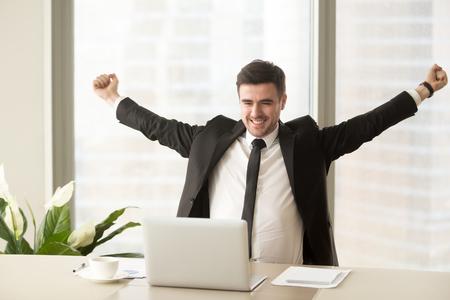 Foto de Happy businessman in suit raising hands looking at laptop, celebrating victory, stock trading win, got job interview invitation, motivated with good work result, achieving goal, business success - Imagen libre de derechos
