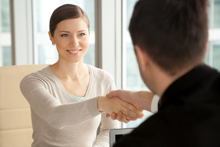 Smiling beautiful woman shaking male hand, greeting handshake of female applicant arriving at job interview, businesswoman making good first impression at meeting with new partner, women in business